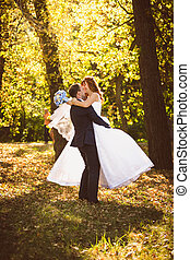 groom in suit hugging and spinning bride at autumn park