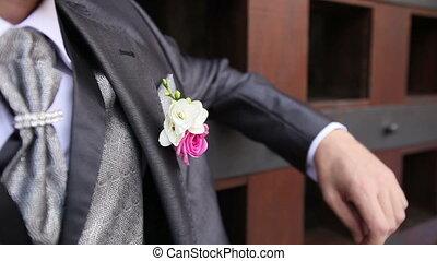groom in wedding suit with flower snaps fingers - groom in...