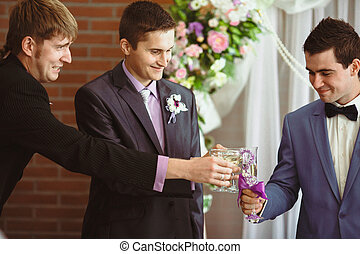 Groom is drinking with his friends on the wedding