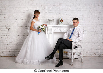 Groom is sitting in a chair and bride is standing near the fireplace in the white brick wall background