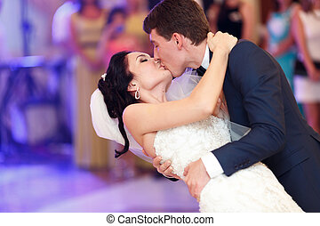Groom kisses a bride bending her over during their first dance