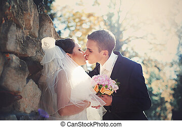 Groom kisses a bride giving her a wedding bouquet