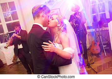 Groom kisses a bride hodling her in his arm during a dance
