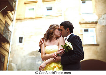 Groom kisses a bride holding her shoulders
