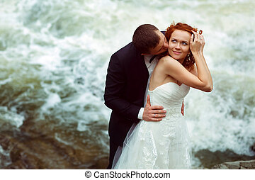 Groom kisses a bride hugging her from behind, standing in the front of foaming mountain river
