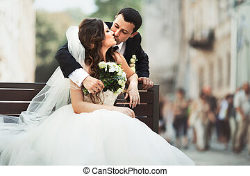 Groom kisses a bride hugging her over the bench