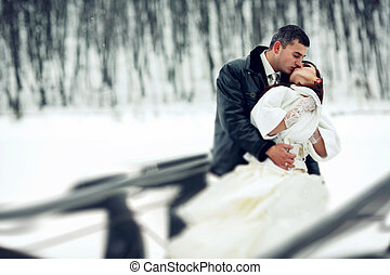 Groom kisses a bride in a white fur coat holding her in his arms in a winter day