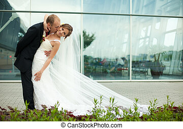 Groom kisses a bride in gorgeous dress bending her over