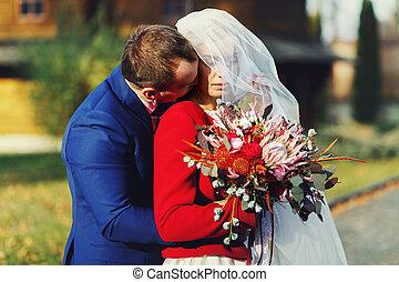 Groom kisses a neck of pretty bride hidden under a veil