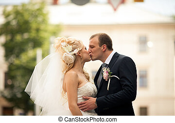Groom kisses bride hugging her delicate waist