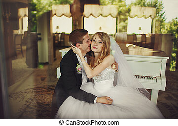 Groom kisses bride's cheek and smiles sitting behind the piano