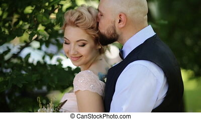 Groom kisses bride's forehead while she leans to him smiling, outdoors