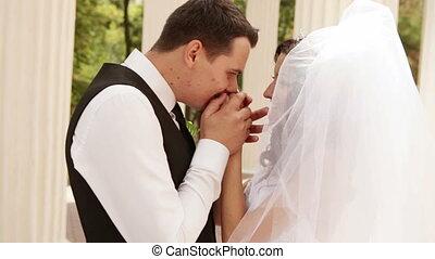 Groom kisses hands bride