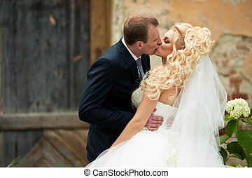Groom kisses passionate bride posing on the street