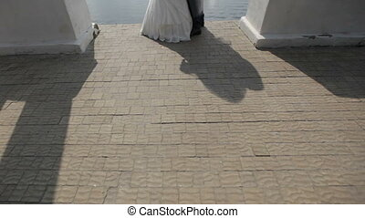 groom kisses the bride against the backdrop of the lake
