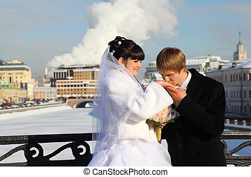 groom kissing bride hand at winter outdoors, couple standing on bridge