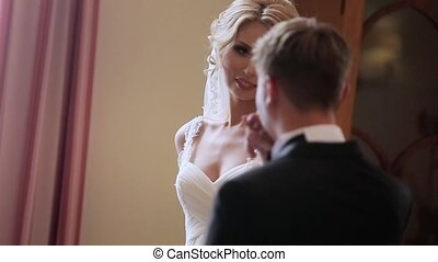 Groom kissing bride's hand in palace hotel indoors