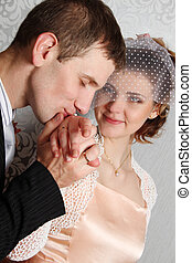 Groom kissing hand of smiling bride