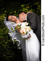 Groom kissing passionately bride in neck neck under tree