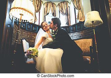 Groom leans bride to himself kissing her cheek in a vintage hall