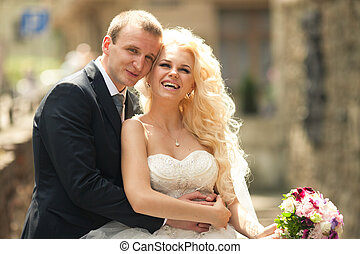 Groom leans to a smiling curly bride