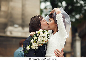 Groom leans to himself a gracious bride kissing her