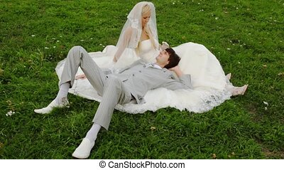 groom lies in lap at bride and on its wedding dress and...