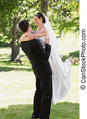 Groom lifting bride in garden
