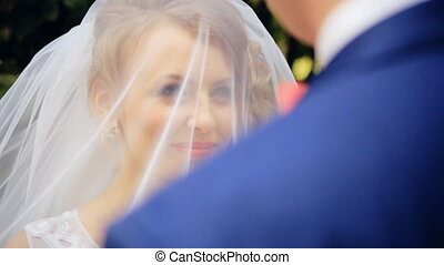 Groom lifting veil off beaming brides face on their wedding day  shot in slow motion  close up