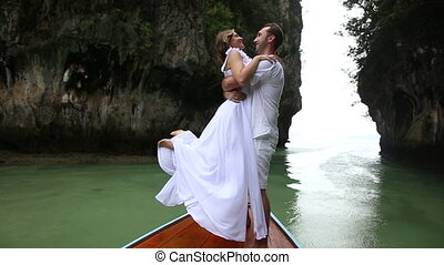 groom lifts bride by waist standing on longtail wooden boat