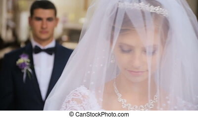 groom lifts veil from face of bride