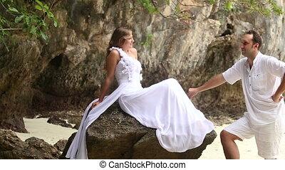 groom look at bride sitting on rock