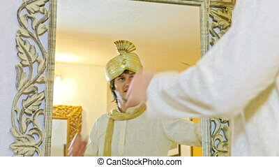 Groom Looks at Himself in Traditional Dress in Mirror -...