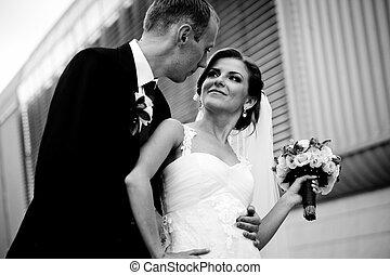 Groom looks in bride's eyes standing in the front of a steel building