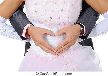 groom make heart fingers