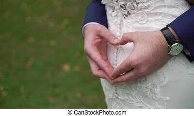 Groom making a heart sign while his arms are around his...