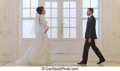 Groom meets bride, hug and whirl her in wedding day