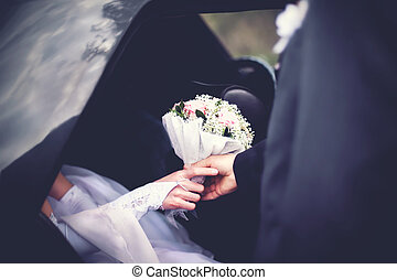 Groom meets the bride from the car with a wedding bouquet of flowers