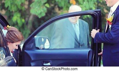 Groom open the door of wedding car and take hand to bride...
