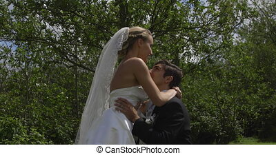 Groom picking up his pretty new wife in a park on their...