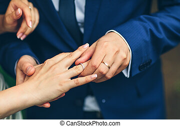 groom placing an engagement ring