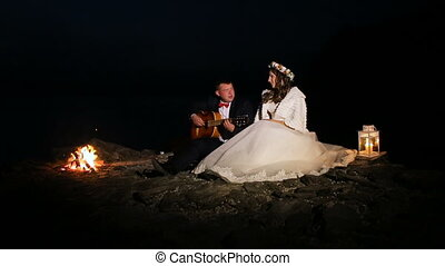 groom playing guitar in the night at campfire