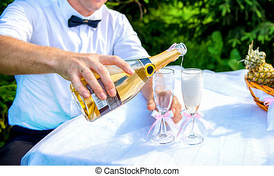 Groom pouring champagne into a glass