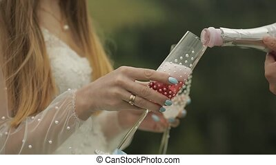 Groom pours pink champagne into the glasses held by the bride