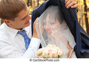 Groom protecting beautiful bride from rain