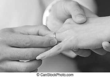 groom put an engagement ring on bride finger