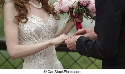 Groom put on wedding ring on bride's hand at wedding...