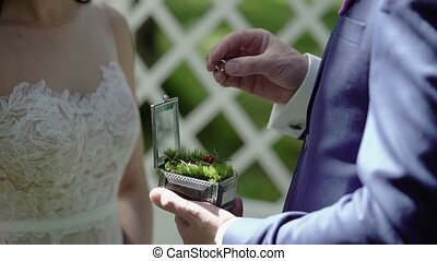 Groom puts on ring to bride hand on ceremony