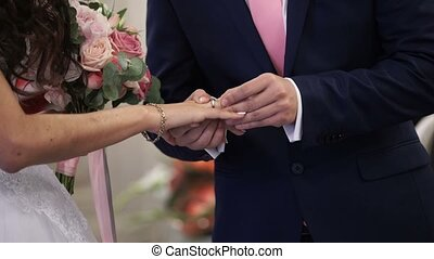 Groom puts on wedding ring on bride hand shot
