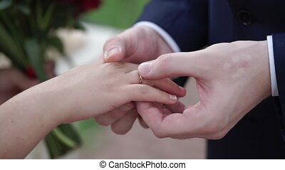 Groom putting a ring on bride's finger during wedding...
